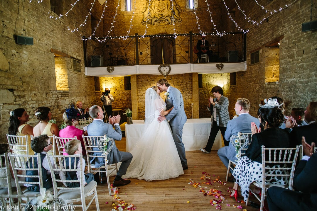 Bride and groom kissing at The great tythe barn wedding ceremony in Gloucestershire