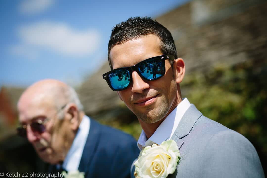 Wedding guest with blue retro sunglasses and yellow rose looking into camera