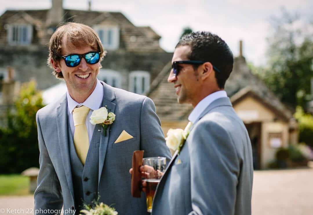 Groom wearing blue sunglasses chatting to wedding guest in Gloucestershire