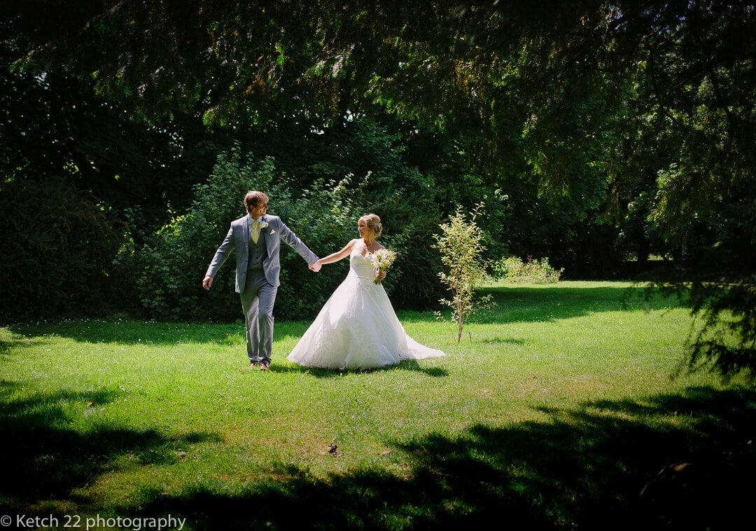 Bride and groom walking through gardens at The great tythe Barn