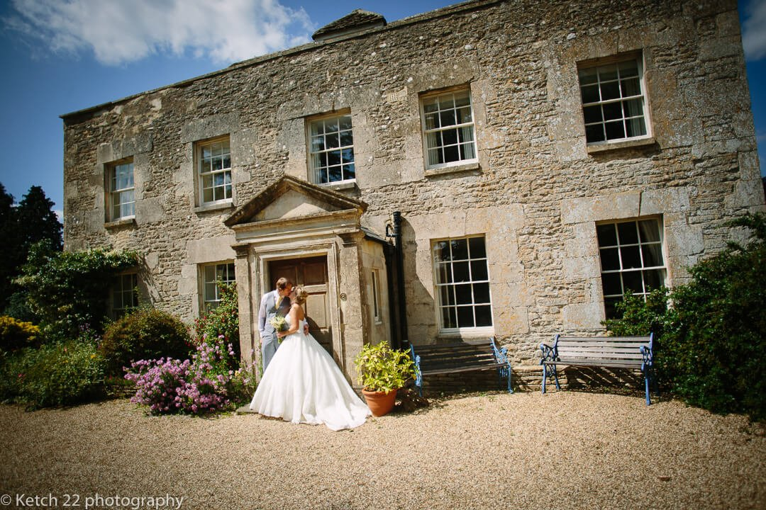 Bride and groom kissing in font of rustic country house at wedding in Gloucestershire