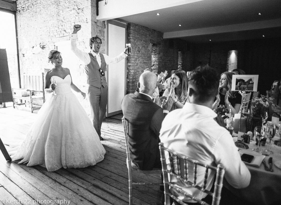 Bride and groom enter dinning room with cheering wedding guests