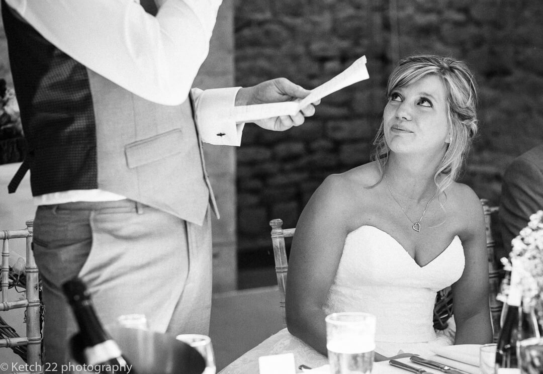 Emotional bride looking at groom making wedding speech at barn wedding
