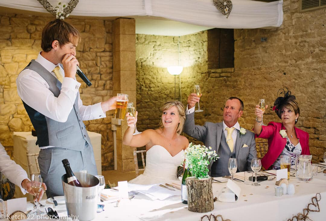 Bride and groom making toast at wedding speech