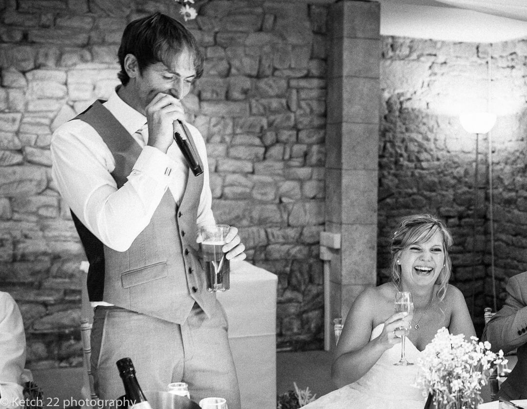 Bride laughing at grooms wedding speech