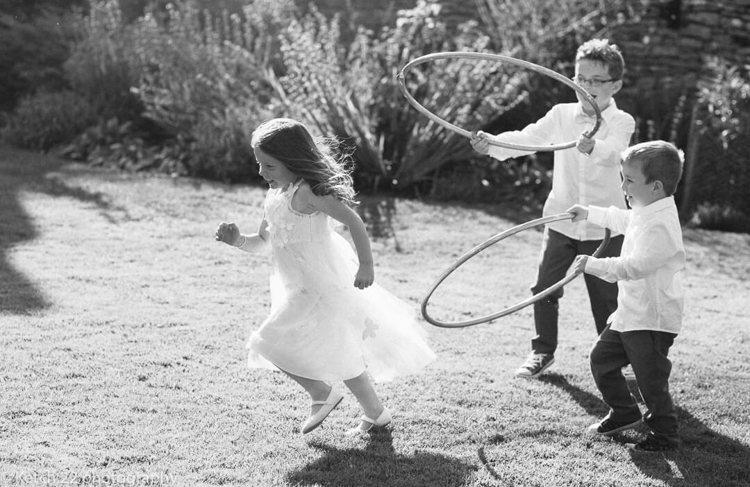 Page girl and page boys playing with hoola hoops at Summer wedding