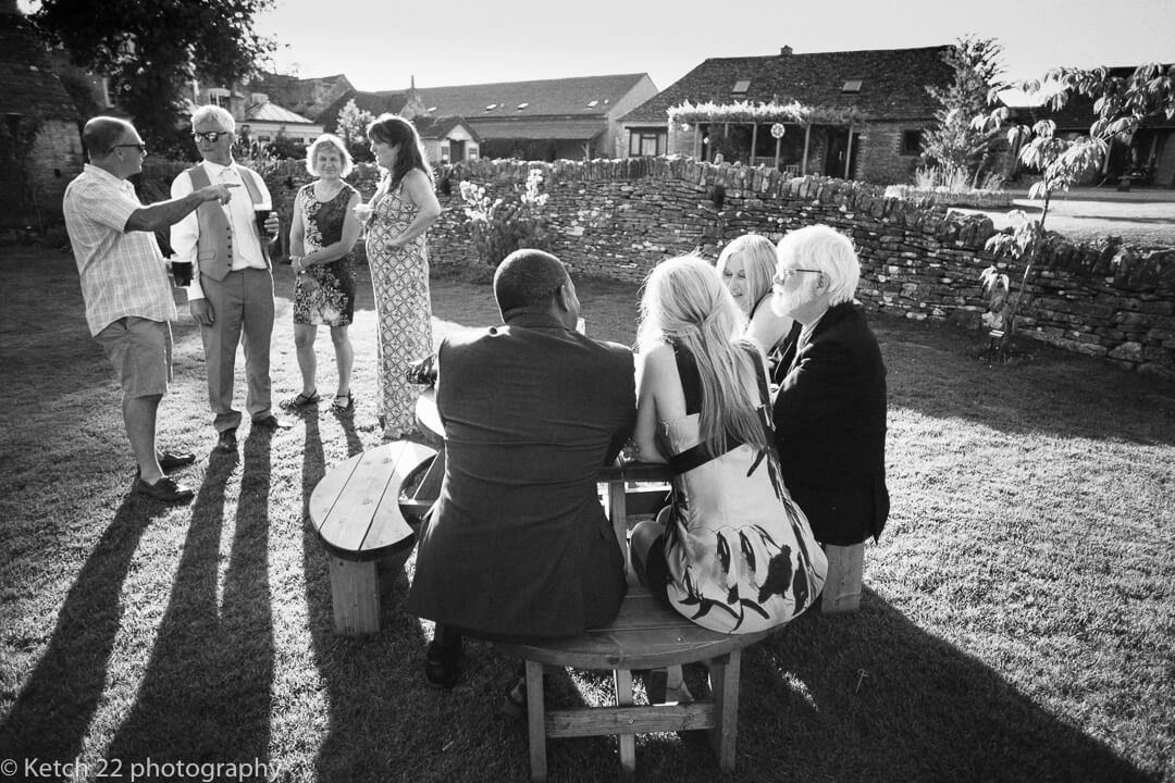 Wedding guests relax in the sun at The Great Tythe Barn