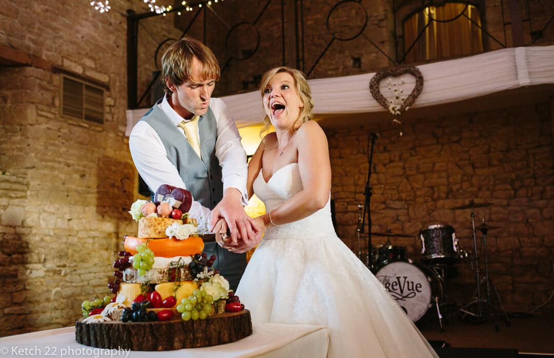 Quirky photo of bride and groom cutting wedding cheese cake at The great tythe Barn in Gloucestershire