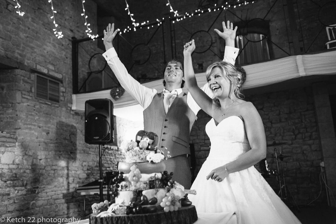 Bride and groom waving at wedding guests after cutting the cake