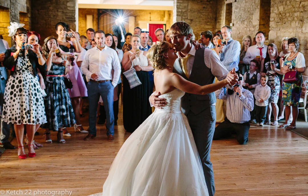 Bride and groom enjoy first dance with wedding guests looking on
