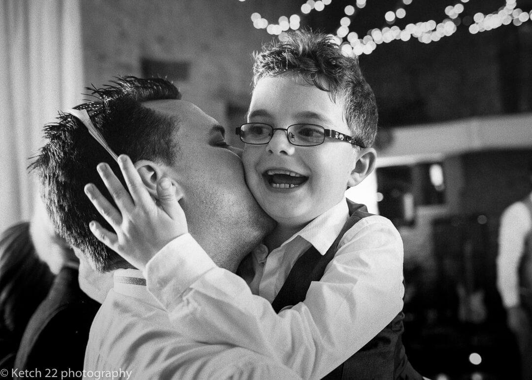 Father hugging page boy at barn wedding