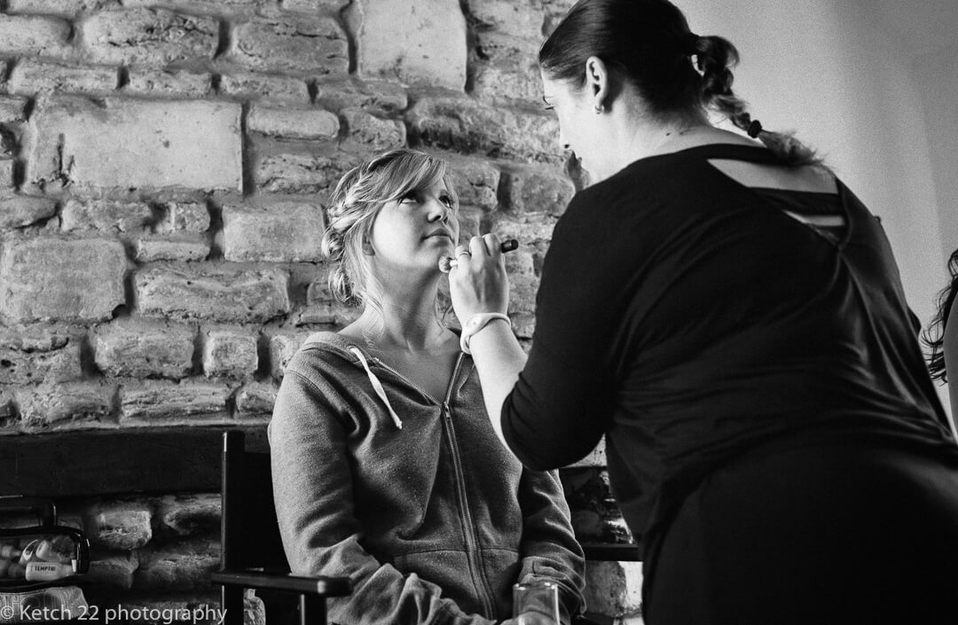 Bride having make up put on at barn wedding