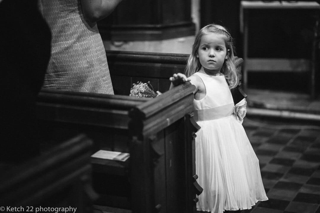 Flower girl looking up at bride as she enters church at Upper Court wedding