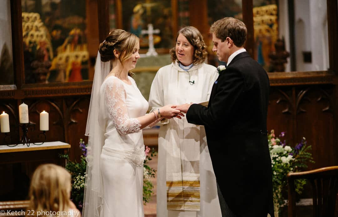 Bride and groom exchanging rings during church wedding ceremony