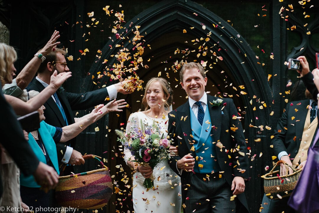 Wedding guests shower bride and groom with confetti