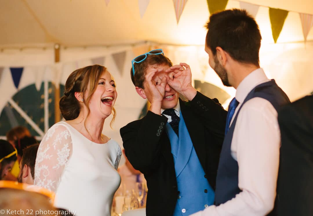 Bride and groom having fun with wedding guest