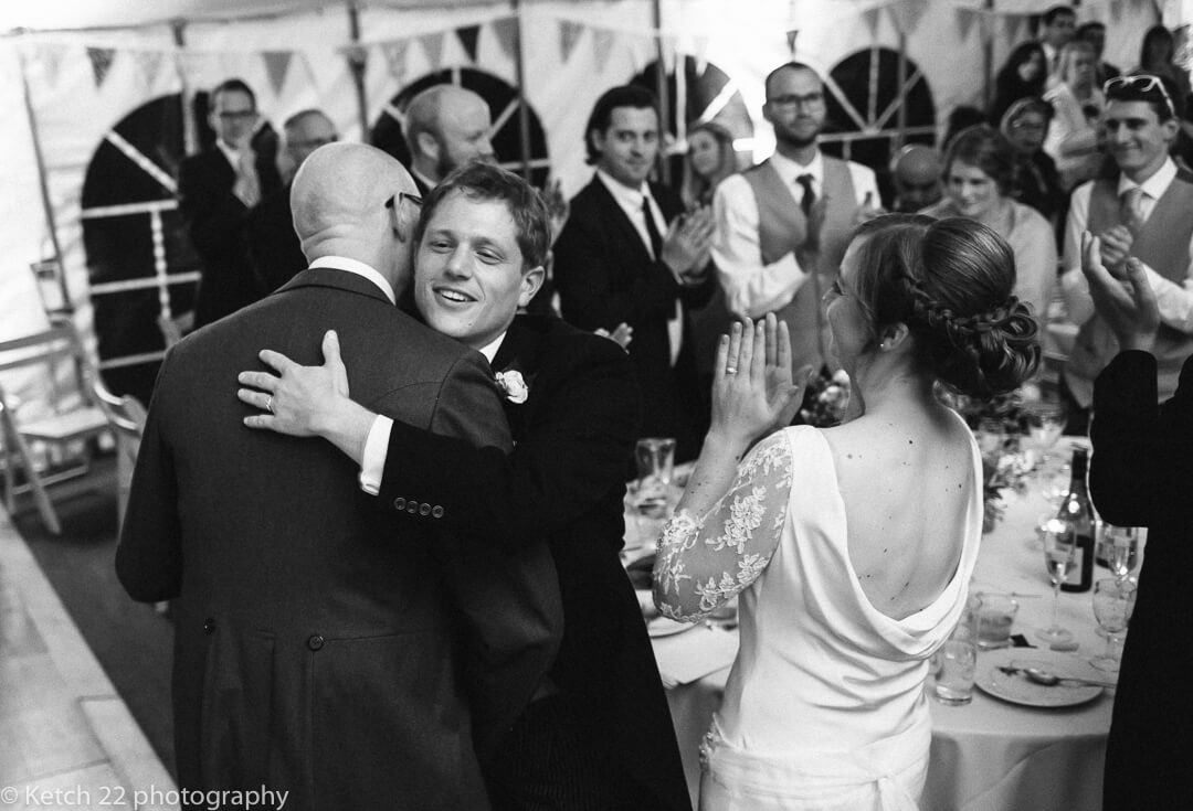 Groom hugging best man after speech at Gloucestershire wedding