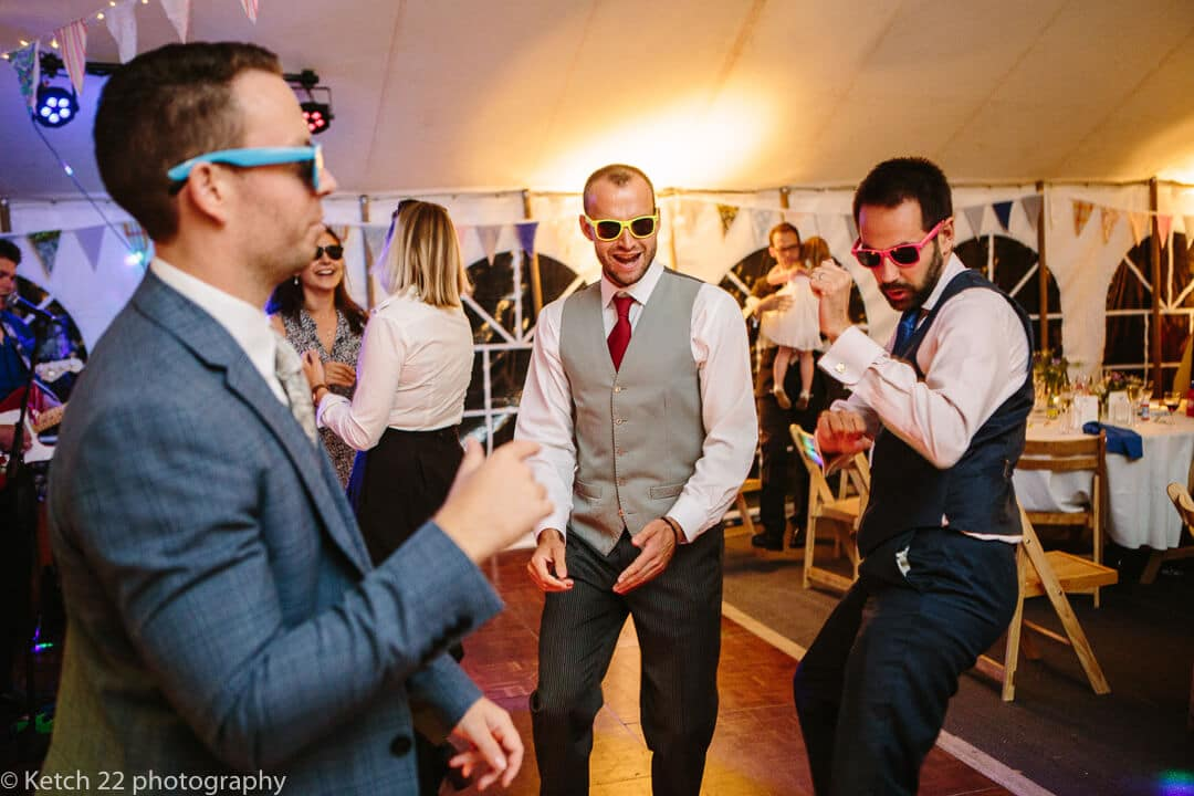 Wedding guests with retro sunglasses dancing