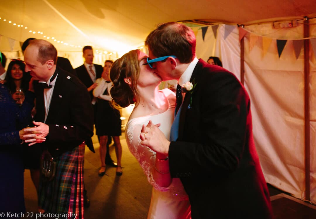 Groom with blue sunglasses kissing bride during first dance