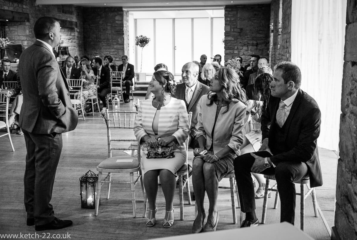 Groom chatting with guests at Weddings at The Great Tythe Barn