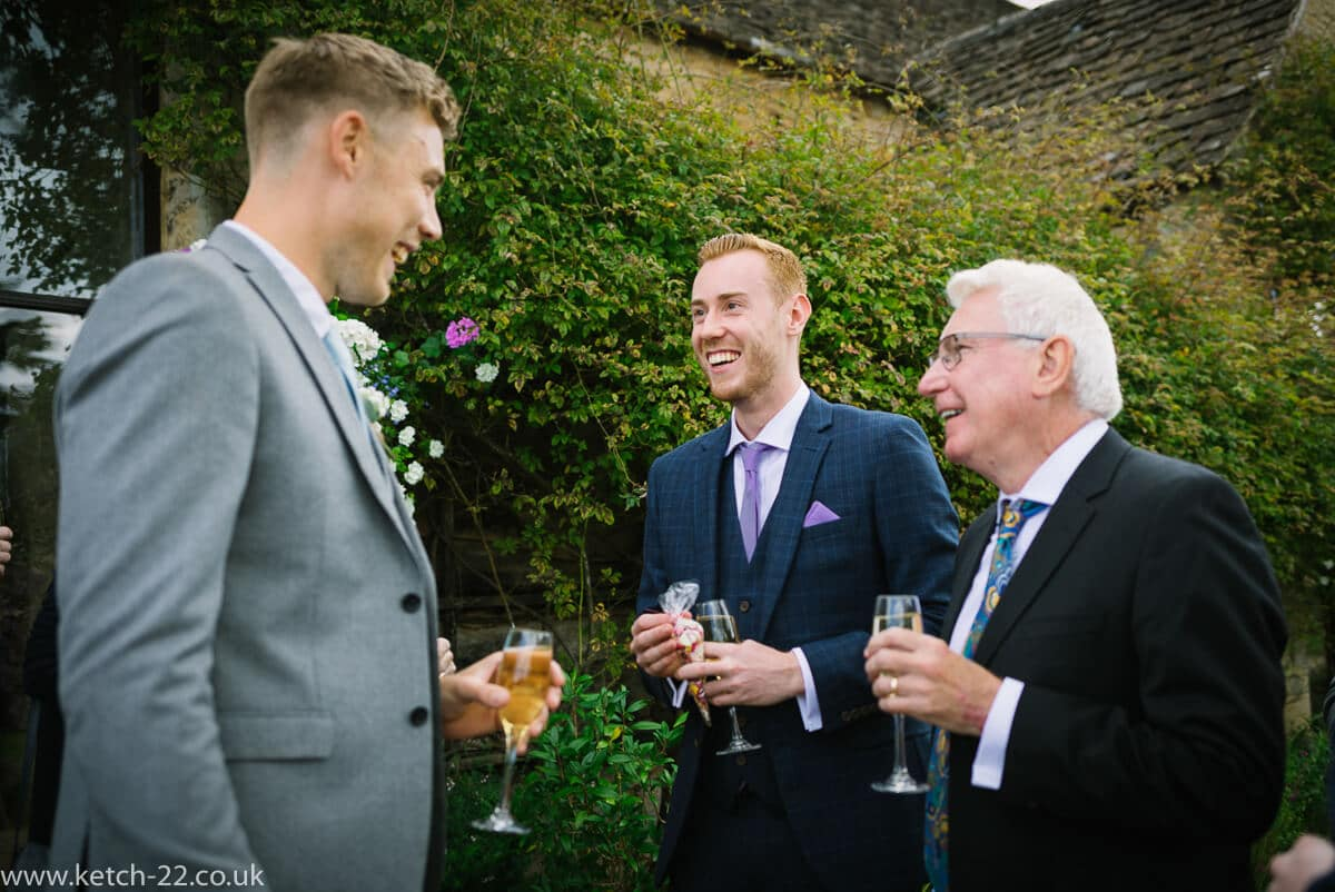 Wedding guests enjoy a drink and a chat in the garden