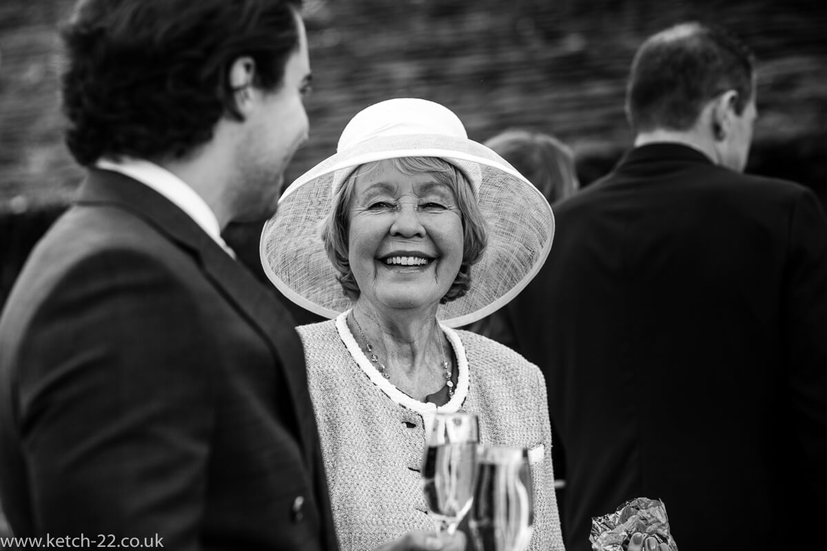 Older lady wedding guest with big white hat chatting