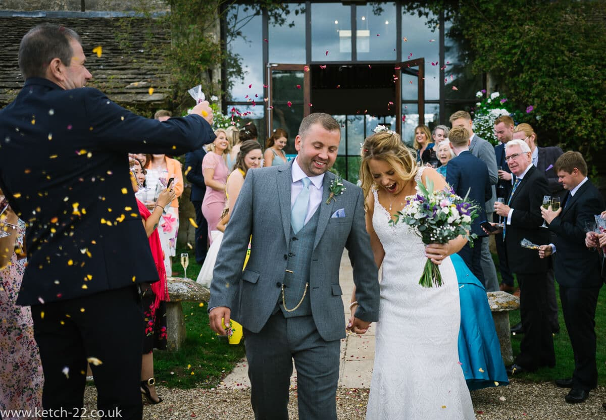 bride and groom walk through confetti at Gloucestershire wedding