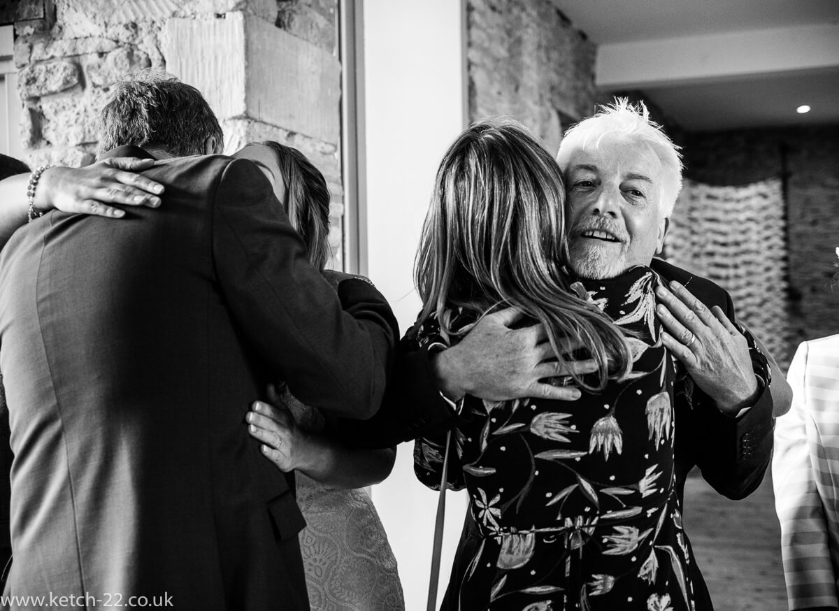 Father of bride hugging guest at Tetbury wedding
