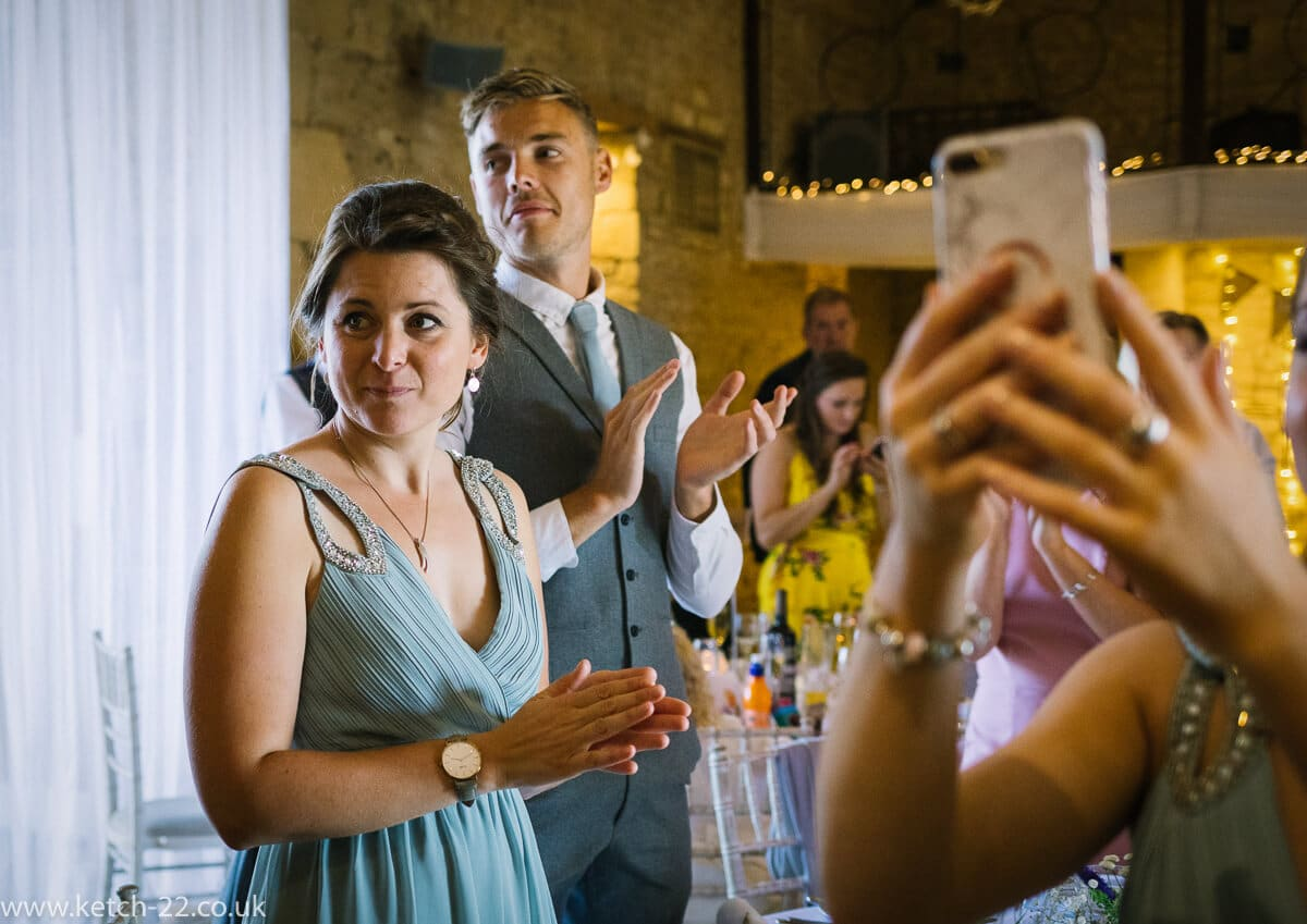 Bridesmaid clapping as bride enters the dining room
