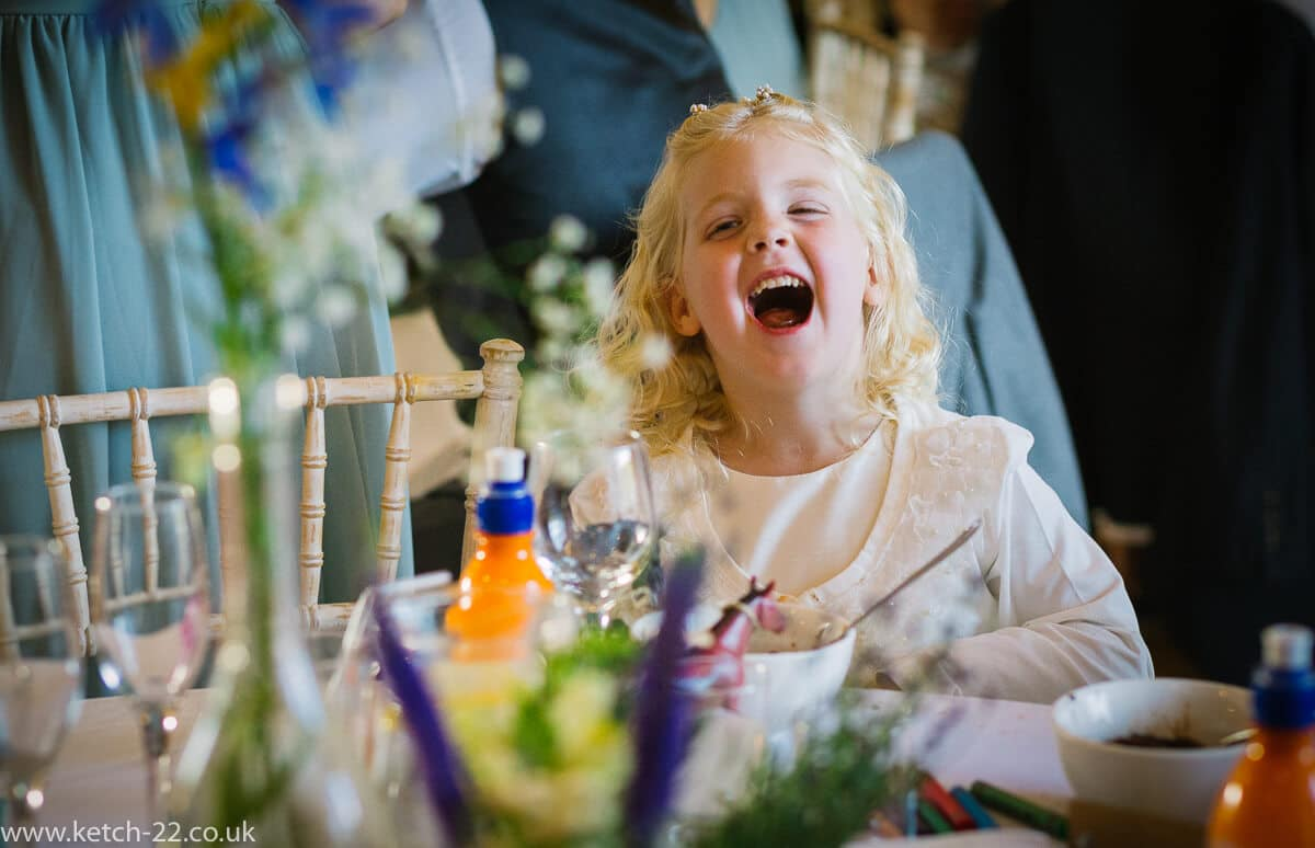 Flower girl laughing during the wedding speeches