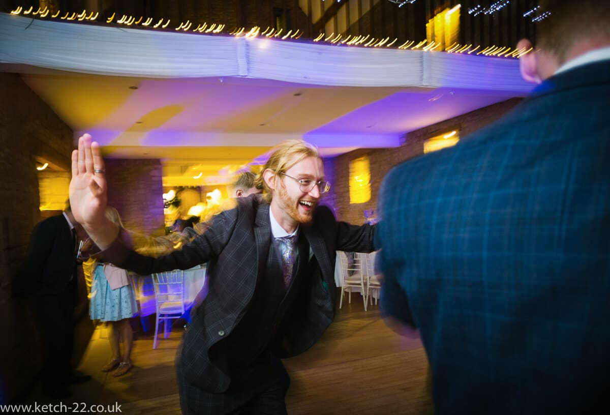 Enthusiastic wedding guest dancing at Wedding at The Great Tythe Barn