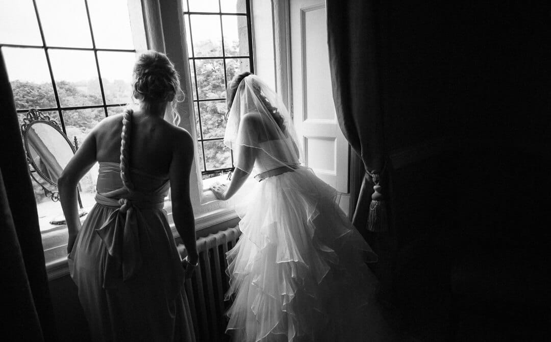 Bride and bridesmaid looking out of window at Clearwell Castle wedding