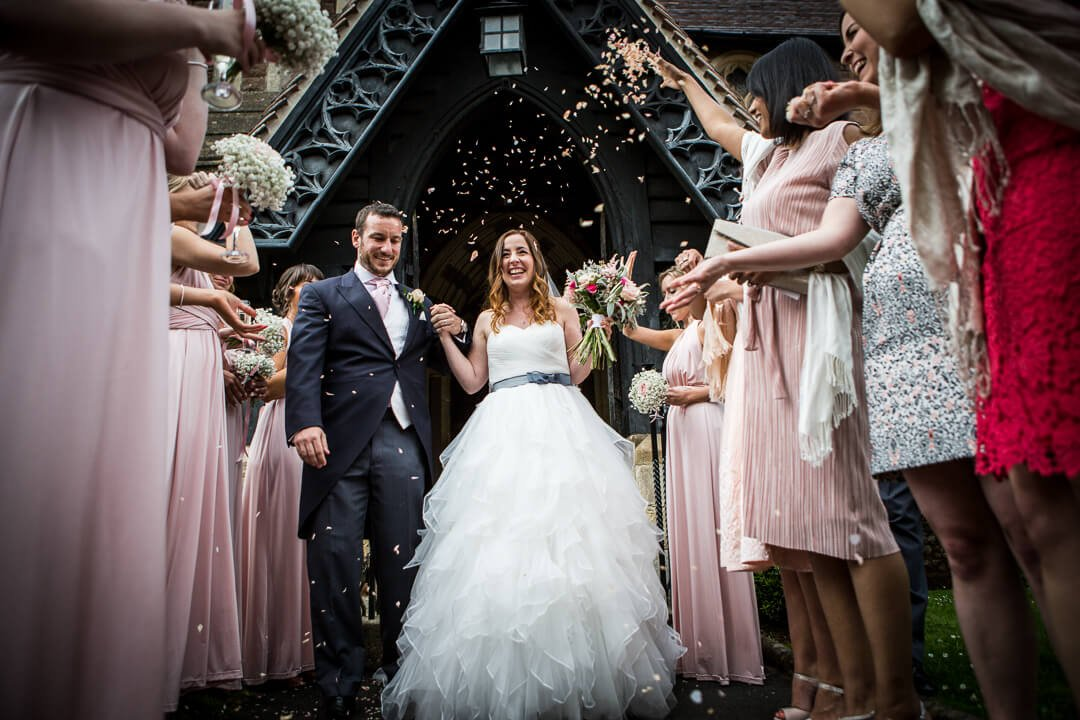 Wedding guests shower newly weds with confetti