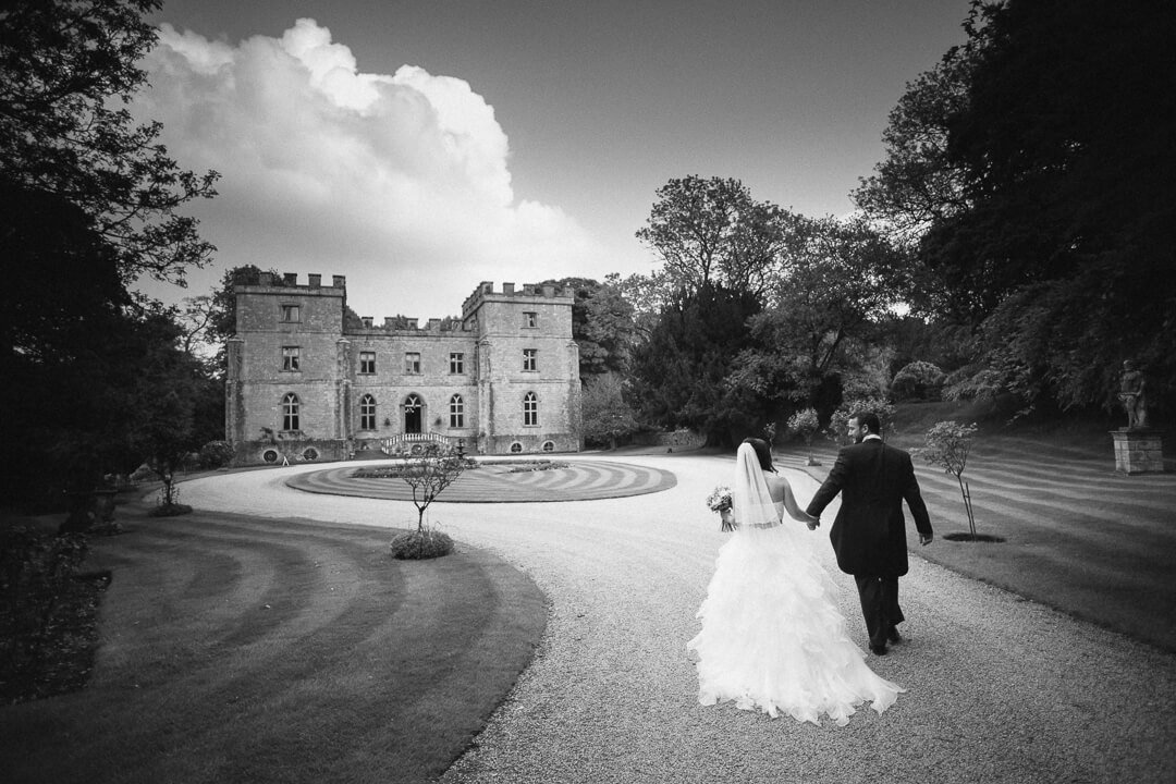 Bride and groom walking in in front of Clearwell Castle wedding venue in Gloucestershire