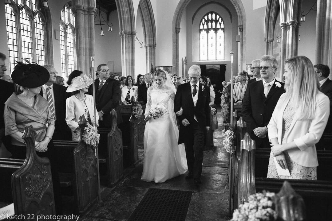 Father and bride walking down Church aisle at church wedding