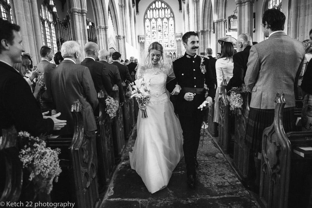 Bride and groom walking down church aisle at wedding