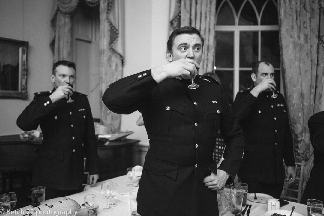 Groomsmen in army uniform toasting the bride