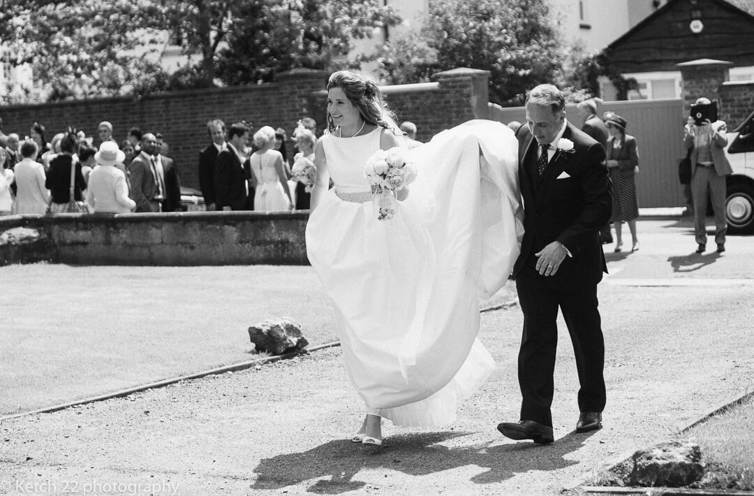 Groom lifting wedding dress for his new bride in Cheltenham