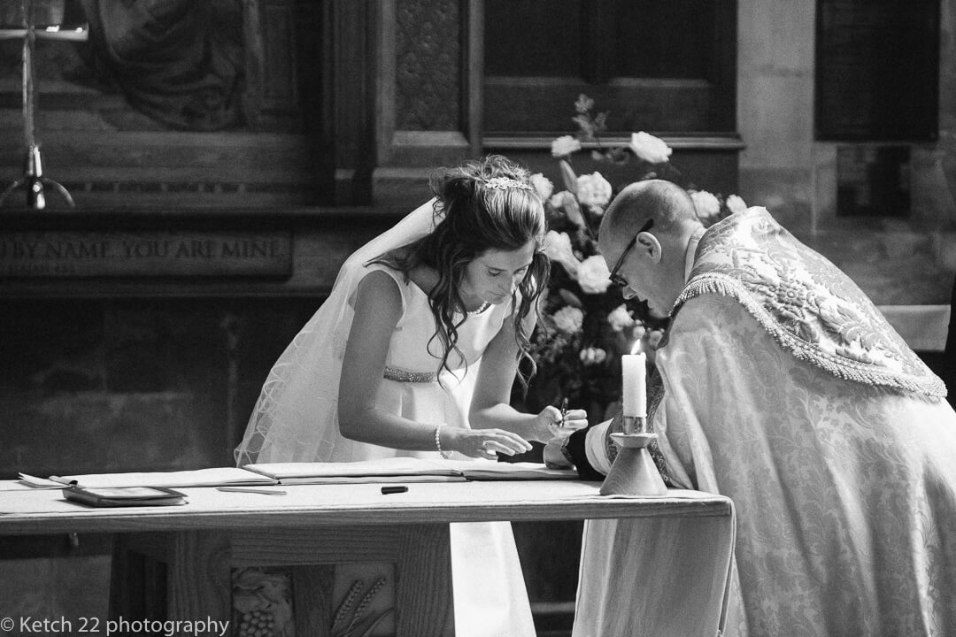 Bride signing the registrar at wedding in church