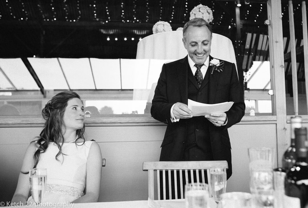 Groom making wedding speech with his bride looking on