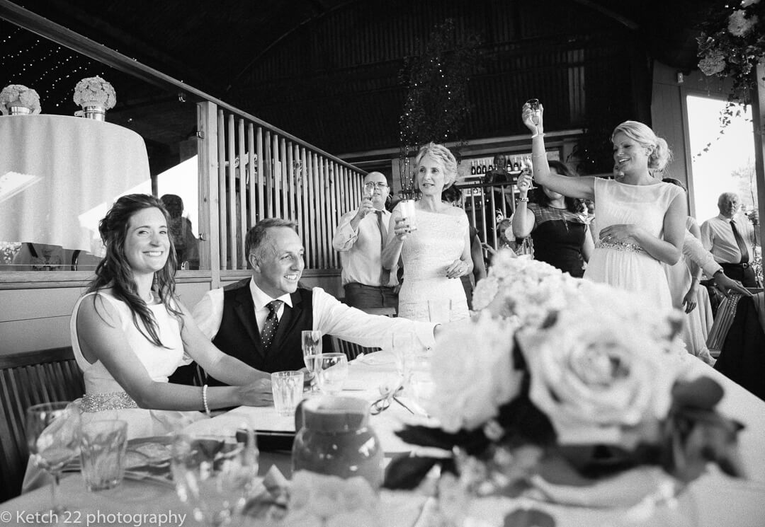 An example of weddings at Cripps Stone Barn Gloucestershire photograph of bride and groom toasting at speeches