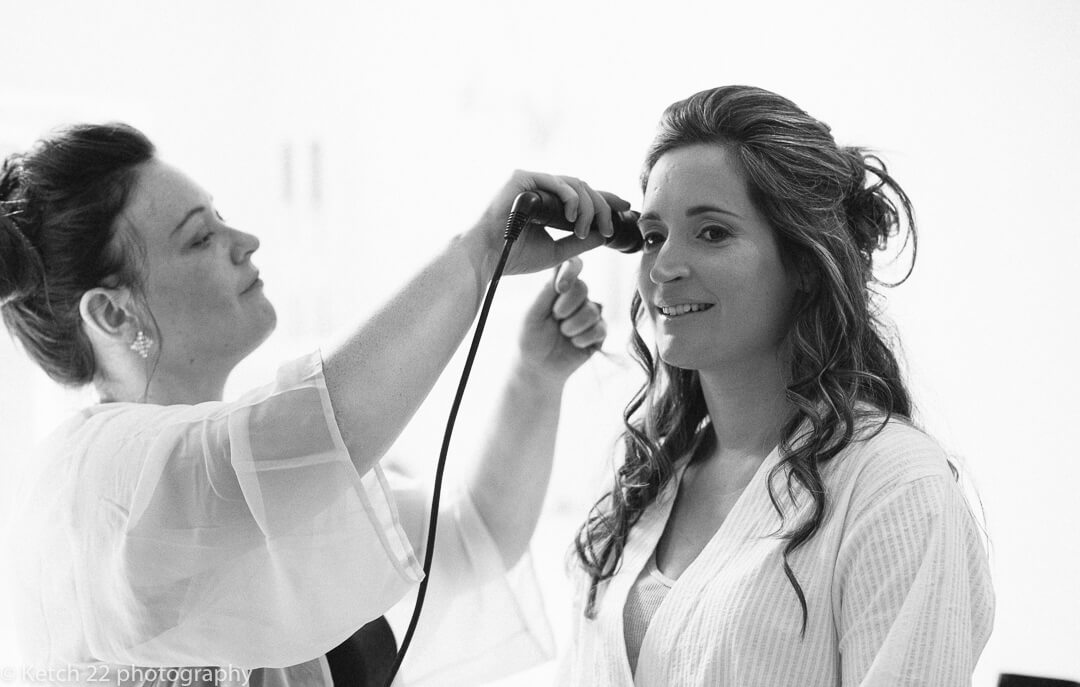 Bride having her hair done at wedding preparations