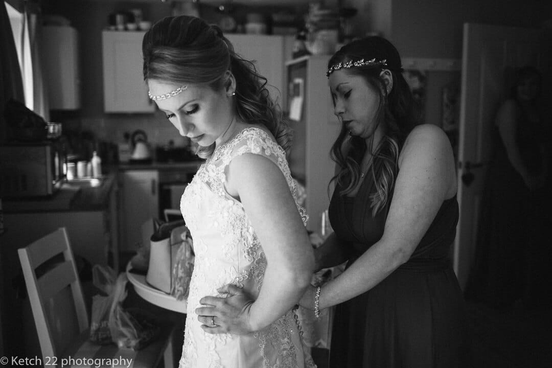 Bride putting on white lace dress at wedding preparations