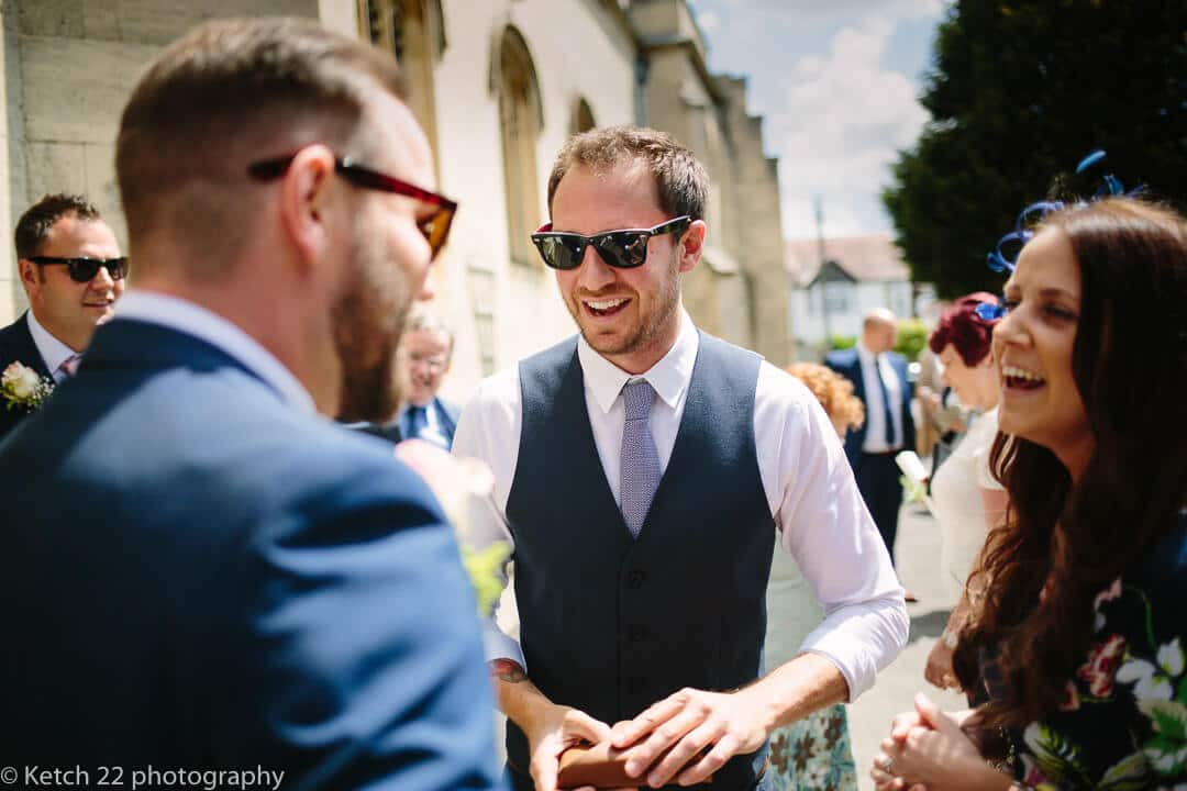 Groom greeting wedding guest at Church wedding in Stroud