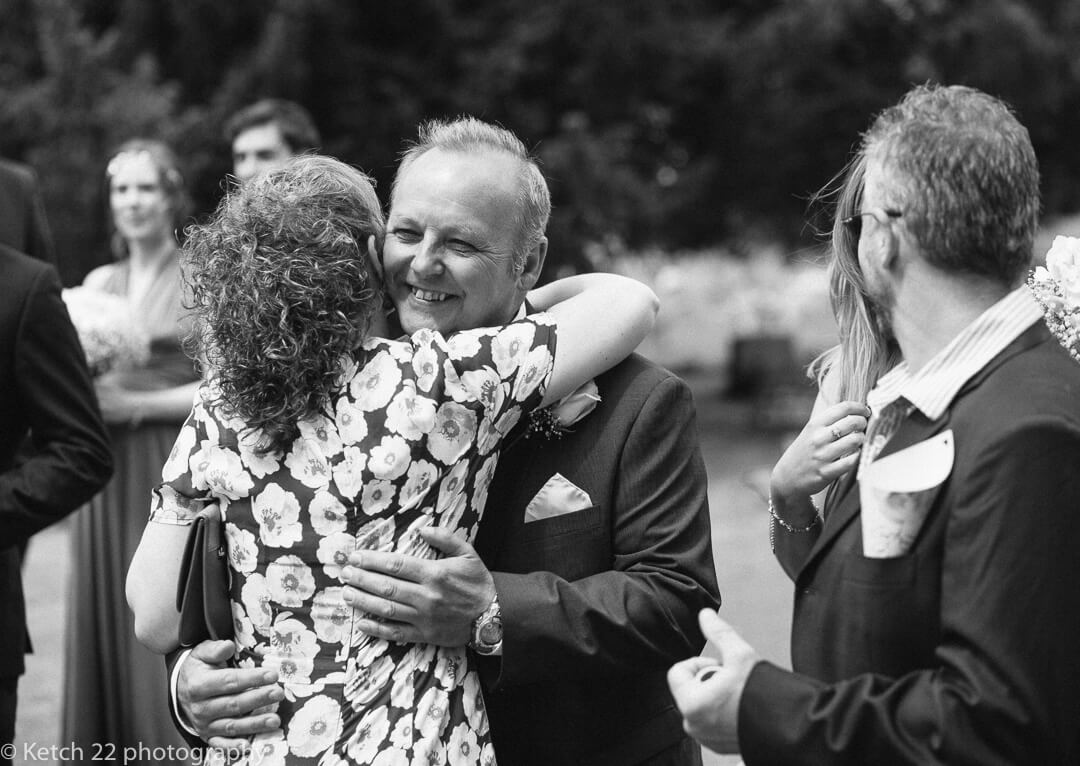 Father of bride hugging wedding guest
