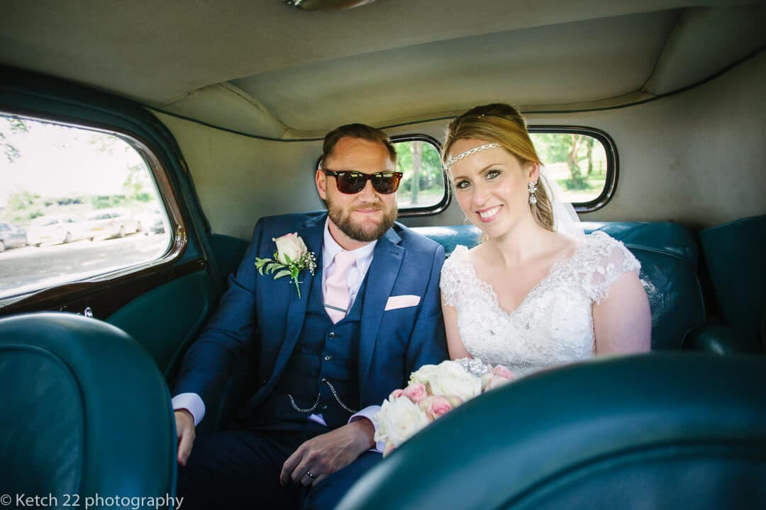 Boho bride and groom in wedding car