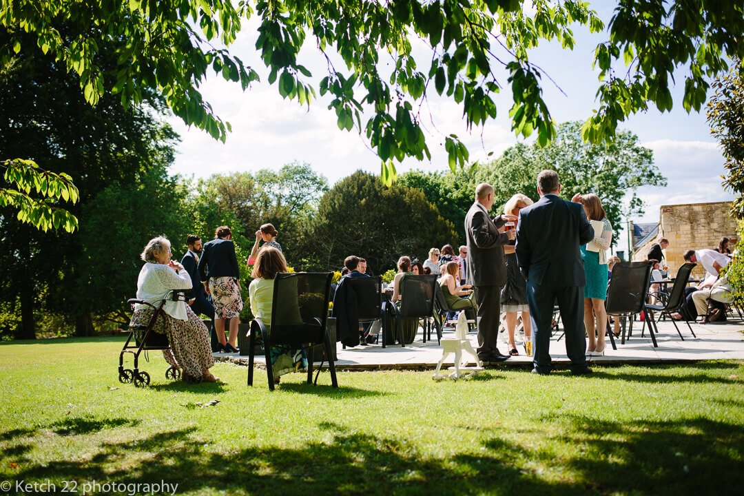 Wedding guests having drinks on lawn at summer wedding in Gloucestershire