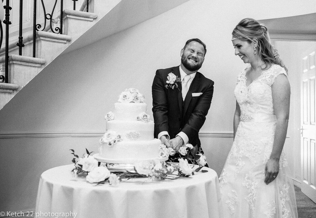 Funny photo of groom cutting the wedding cake