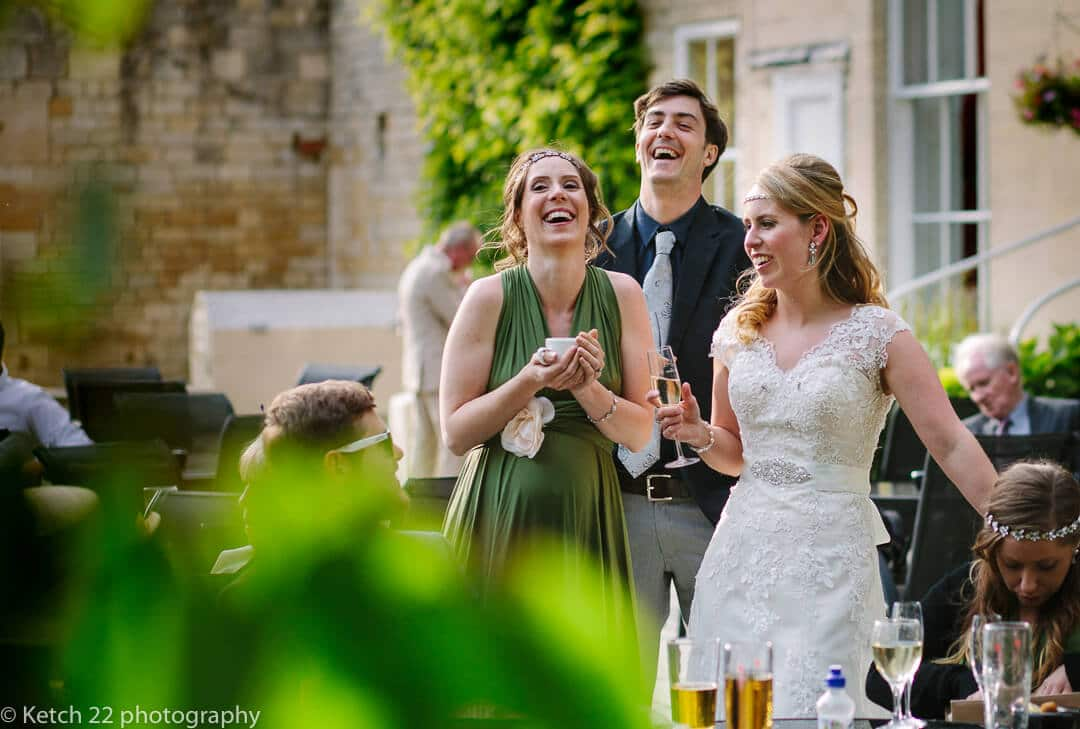 Bride laughing with wedding guests in garden at rural wedding