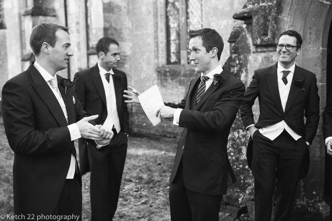 Groom and groomsmen chatting outside church just prior to wedding ceremony